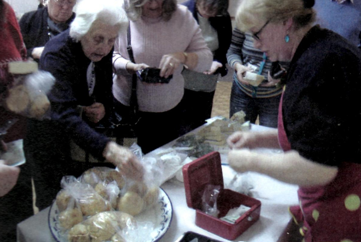 Photograph of people buying cheese & cheese scones after the talk on the History of Cheese